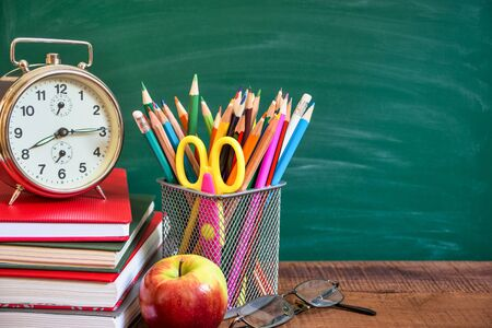 Photo pour School supplies, alarm clock, apple and books on wooden table in front of the school chalkboard. Back to school concept. - image libre de droit