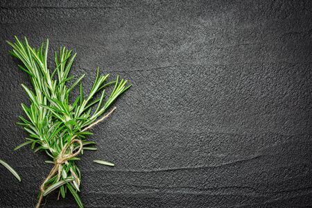 Photo for Fresh rosemary branches on black stone background. Top view with copy space. - Royalty Free Image