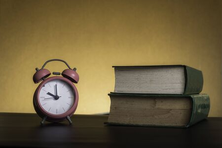 Photo pour Symbolic hard study is powerful to succeed, concept with book and alarm clock. Time in business and quality - image libre de droit