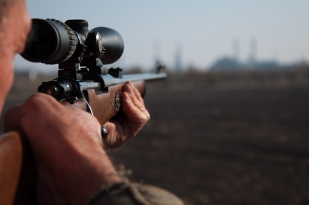 Photo pour Hunter aiming with sniper rifle in the field - image libre de droit