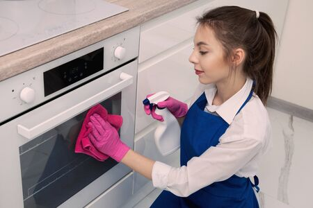 Photo pour Beautiful young girl washes an oven with detergent. - image libre de droit