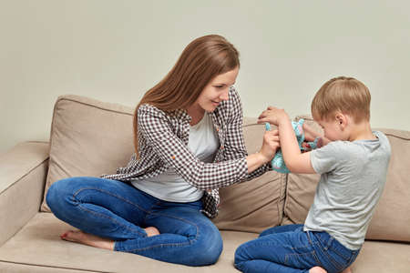 Foto für Mother playing with little son, mom enjoying the weekend time with preschool cheerful child, laughing together, sitting on the sofa at home, having fun, activities with the child at home. - Lizenzfreies Bild