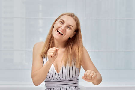 Pretty smiling joyfully woman with long blond hair looking contentedly at the camera, being happy. Studio shot of a beautiful woman.