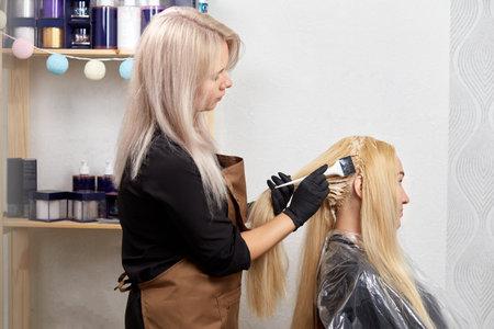 Foto für Hair coloring for a client in a beauty salon. Coloring light hair. Professional hair care products. - Lizenzfreies Bild