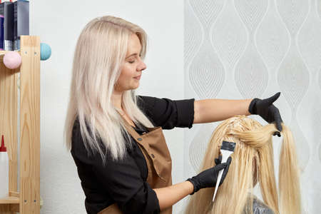 Foto für A female hairdresser in black gloves paints the hair roots of a blonde client with a brush. Professional hair care products. - Lizenzfreies Bild
