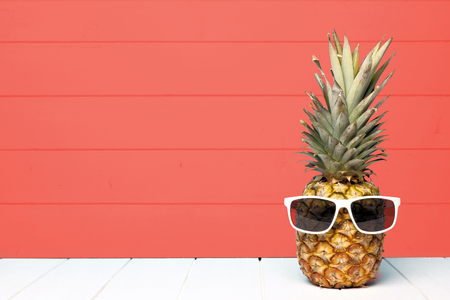Photo for Hipster pineapple with sunglasses against a living coral colored wood background - Royalty Free Image