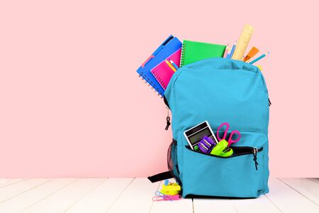 Photo for Blue backpack full of school supplies against a pink background, back to school concept - Royalty Free Image