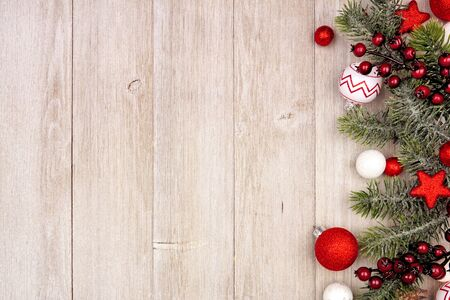 Photo pour Christmas side border with red and white ornaments and branches, above view on a gray wood background - image libre de droit