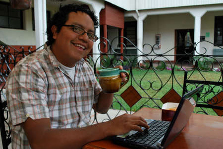 Hispanic man sipping coffee and working on his laptop computer