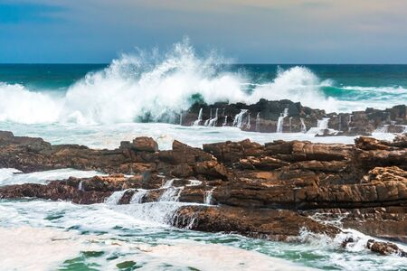 Waves crashing wildly on the rocky shore at Storms River Mouth, Tsitsikamma National Park, South Africa