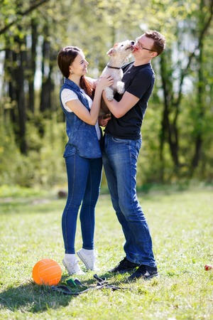 couple and dog licking his owner in face as a sign of affection