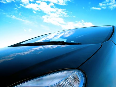 close up of a frontside of a car under a cloudy blue sky