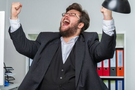 Foto de A person in an office bursts out in jubilation and pulls his arms up in the air - Imagen libre de derechos