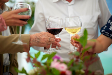 Soft focus at group elderly hands holding wine glass and clink glasses. Concept of older party , retire and superannuate people, sixtieth anniversary of age.