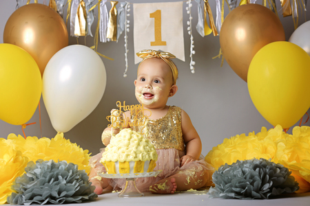 Foto de little girl with brown eyes with a bandage on her head and a beautiful dress crawling on the floor next to balloons and a cake marking her first birthday. - Imagen libre de derechos
