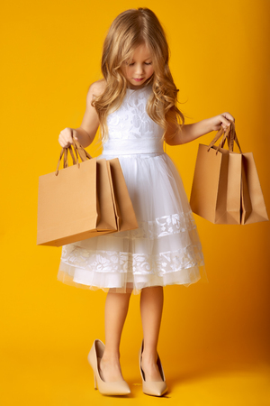 Foto de Amazed attractive child in dress and big shoes holding shopping bags on yellow background. KIDS FASHION - Imagen libre de derechos