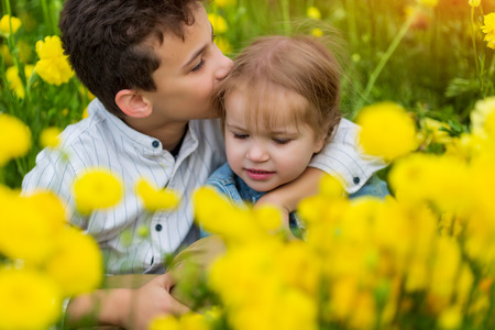 Photo for older brother hugs and kisses his younger sister, in the field in yellow flowers - Royalty Free Image