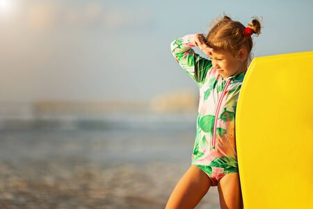 Foto per Summer Travel Beach Vacation. Beautiful little girl in a swimsuit With Surfboard - Immagine Royalty Free