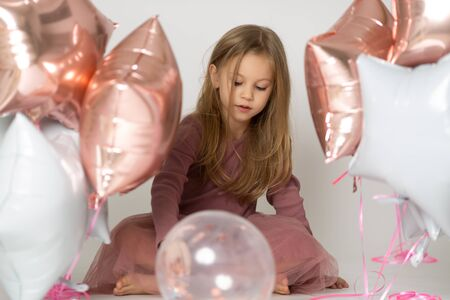 Photo for Sweet little girl with air balloons in studio - Royalty Free Image