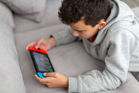 Photo pour Teenager lies on a sofa and plays a game. He has a portable game console in his hands. How teens spend their vacations. - image libre de droit