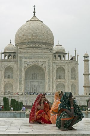 Agra, Uttar Pradesh, India - July 26, 2008: Indian ladies in colorful sari's squatting on a white marble plinth at the Taj Mahal in Agra, Uttar Pradesh, India