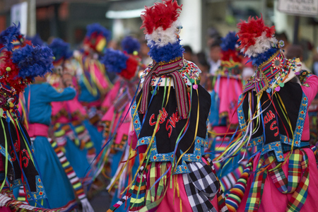 ARICA, CHILE - JANUARY 24, 2016: Tinku dancing group in colourful costumes performing a traditional ritual dance as part of the Carnaval Andino con la Fuerza del Sol in Arica, Chile.