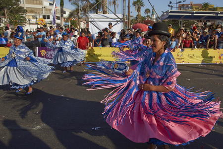 ARICA, CHILE - FEBRUARY 10, 2017: Female members of a Morenada dance group in ornate costumes performing at the annual Carnaval Andino con la Fuerza del Sol in Arica, Chile.