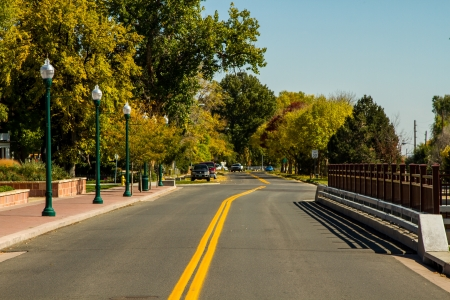 Tree lined street in Boulder, Colorado with no traffic, and green rustic street lights