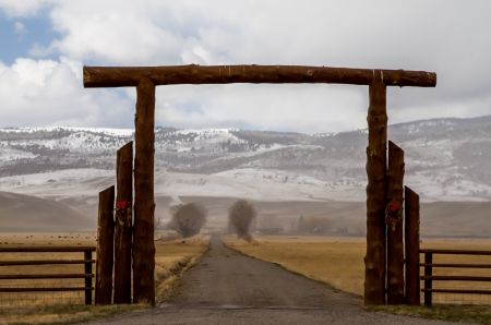 Big log gate over lane to Montana cattle ranch in the winter