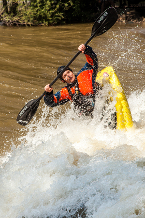 Salida, USA - June 20, 2015: Professional freestyle kayaker at the 2015 FIBArk Freestyle Whitewater Rodeo competiton at Riverside Park, Arkansas River, Salida, Colorado. This kayaker is competing for points in the Freestyle Pro Semi-Finals event.