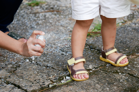 Foto de Mother spraying insect or mosquito repellents on skin girl, mosquito repellent for babies, toddlers that will protect your children from mosquitoes and other insects. - Imagen libre de derechos