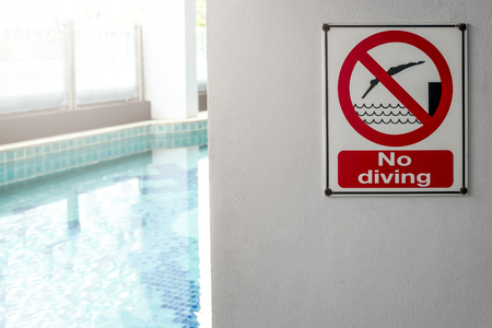 Photo for No diving sign at the poolside warning on blurred swimming pool - Royalty Free Image