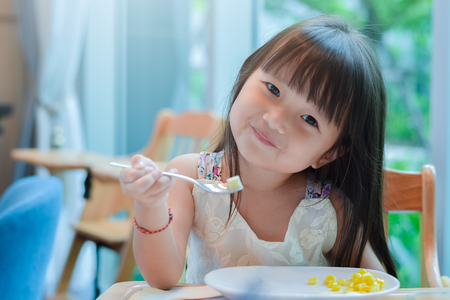 Foto de Little asian child girl having breakfast at the morning with a happy smiling face and showing food on a spoon. - Imagen libre de derechos