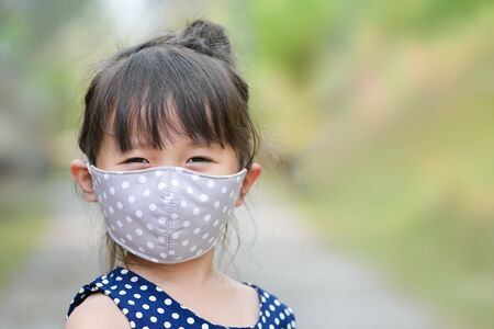 Photo pour Little girl has fabric mask protect herself from Coronavirus COVID-19,hand stop sign when child leave the house,,child with a mask on her nose for safety outdoor activity,illness or Air pollution - image libre de droit