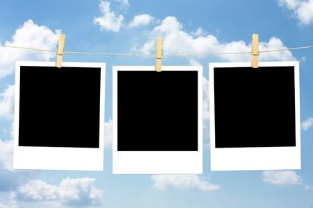 Three blank polaroid photos against blue sky