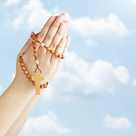 Hand with a rosary against blue sky