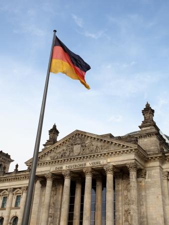 Reichstag in Berlin wih German flag against blue sky