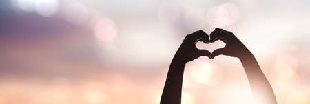 Foto de female hands silhouette in a heart shape - Imagen libre de derechos