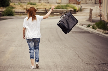 Young girl throws her suitcase walking down the street. Rear view