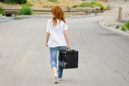 Young girl with old suitcase walking down the street. Rear view