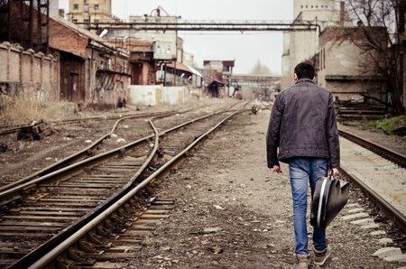 Young man with guitar case in hand is going away among industrial ruins