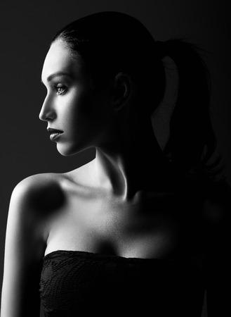 Photo pour Studio shot: dramatic portrait of a beautiful young woman. Profile view. Black and white - image libre de droit