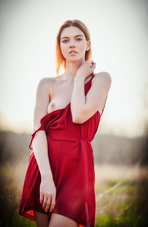 Portrait of a sexy young woman wearing red dress in the field at sunset. Topless