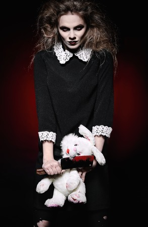 Horror shot: a scary wicked girl with rabbit toy and bloody knife in hands