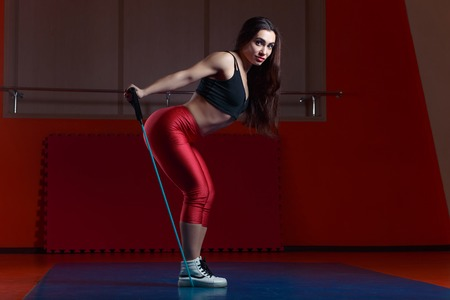 Young attractive muscular fitness woman doing exercise with stra