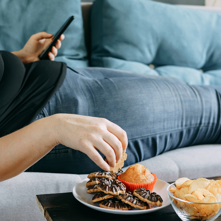 Overweight woman laying on sofa eating sugary food
