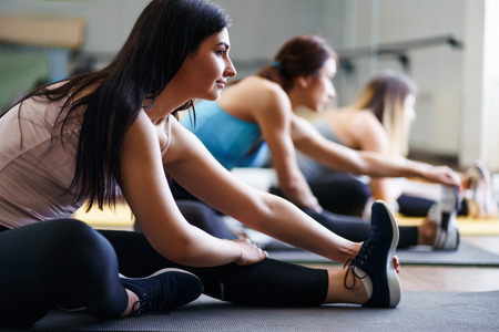 Photo for Sporty women stretching during yoga class - Royalty Free Image