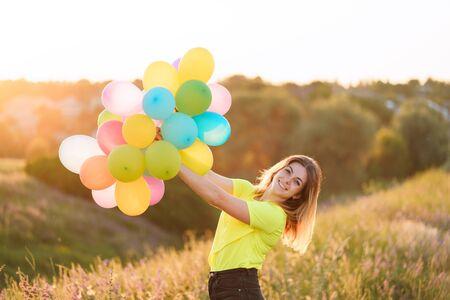 Foto de happy woman with multicolored balloons at sunset - Imagen libre de derechos