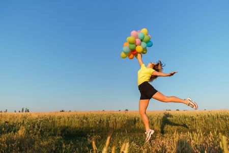 Photo pour Happy woman jumping with multicolored balloons - image libre de droit