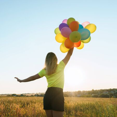 Photo pour Young woman with colorful balloons in summer field - image libre de droit